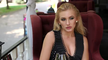 divas : Elegant blue-eyed blonde sitting in a street summer cafe with a glass of red wine. Slow motion.