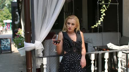 divas : Sexy young girl in an elegant dress is in a cafe leaning on the railing with a glass of red wine. Slow motion.