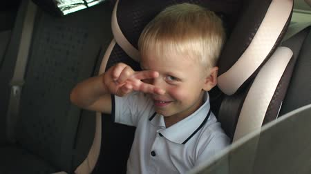 csattanás : Cute cheerful kid is playing and having fun in the kids car seat during the summer journey, slow motion. Child transportation safety.