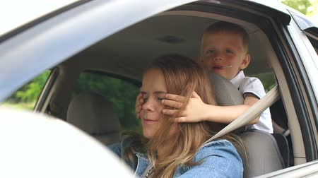 ignore : Naughty kid interferes with mom who is driving a car, he closes her eyes with his hands. Danger while driving. The child is not wearing seat belts. Close-up. Slow motion.