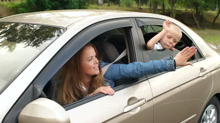 řídit : Happy mother with a young son traveling by car. A young woman and a child look out of the car window and slap each other on the arm. Slow motion. Mom and son having fun in the car. Dostupné videozáznamy