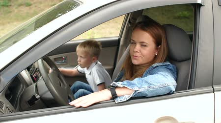 parentes : Portrait of a young woman with a child in the car in the front seat. Mother and son sitting in the car, the child eats candy. Slow motion.