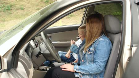 леденец : Mother and son are sitting in the car in the front seat, the child eats candy on a stick and the woman takes the candy for herself. Slow motion. The child is not wearing seat belts.