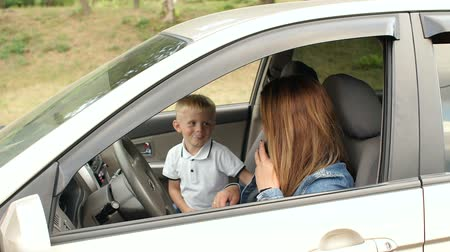 carelessness : A naughty child indulges in a car sitting in the front seat, he is not fastened and prevents his mother from talking on the phone. Kid interferes with mom in a car, he closes her eyes with his hands.