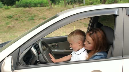 bérlet : Cute curious small boy sitting on his mothers lap behind the steering wheel, he presses the horn and is genuinely pleased with the signal. Portrait of a young mom with her son driving a car. Stock mozgókép