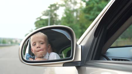 retrovisore : Close-up reflection in the side mirror in the car of a little boy with his mother, the child is playing in the car sitting behind the wheel. Slow motion.