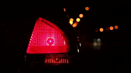 размеры : Close-up flashing yellow rear light on the car at night. Slow motion. Red headlights dimensions on a car at night with a flashing yellow light emergency lights or turns. Стоковые видеозаписи