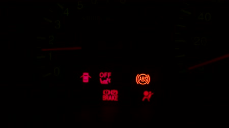 brake : Red and yellow car warning signs on modern car dashboard on black background. Red warning car signs on dashboard, close-up view. Stock Footage
