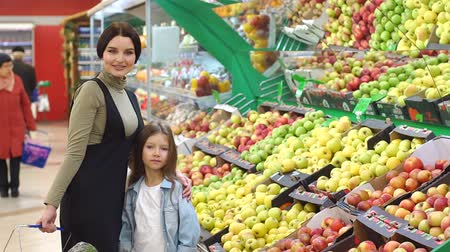 mercearia : Mother and daughter in produce section of supermarket. Woman and little girl choosing apple during shopping at fruit vegetable supermarket.Young mother and her daughter selecting fruits in supermarket