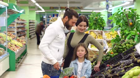 beringela : A young family with a cute daughter buy vegetables in the supermarket, they talk and smile choosing eggplants and radishes. Slow motion. The concept of shopping.