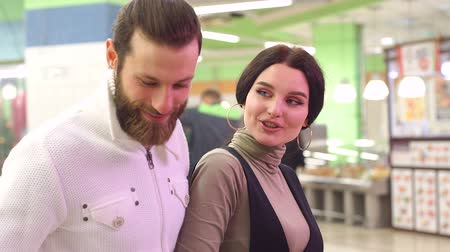 obyčejný : Beautiful young couple is choosing products and smiling while doing shopping at the supermarket. Couple is choosing frozen seafood for dinner in the supermarket.