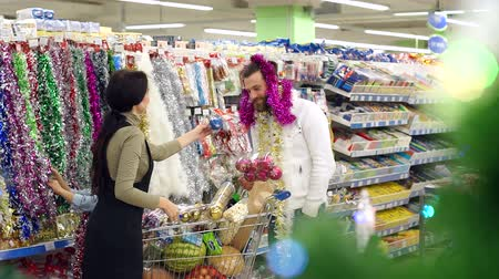 korale : Happy loving couple buying Christmas decorations and gifts for Christmas. The girl puts a garland on her boyfriends head, the couple is having fun at the Christmas holidays in the supermarket.Slow mo