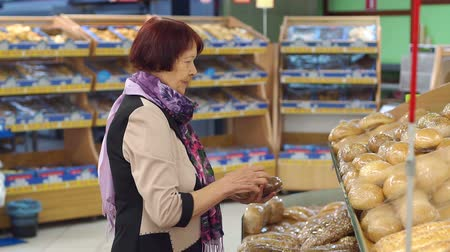 lista de la compra : A senior woman of age buys bread at the supermarket. Grandmother of eighty years picks and buys bread at the grocery store. Slow motion.