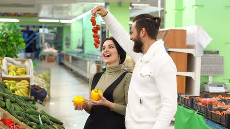 corredor : Shopping, food, sale, consumerism and people concept - happy couple buying pepper and tomatoes at grocery store or supermarket. Enjoying time in supermarket. Slow motion.