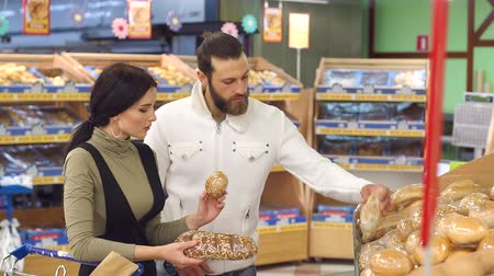 mindennapi : Portrait of a young couple with a full trolley of products in the supermarket. Portrait of family shopping for groceries in supermarket together, while choosing fresh bread loaf in bakery department. Stock mozgókép