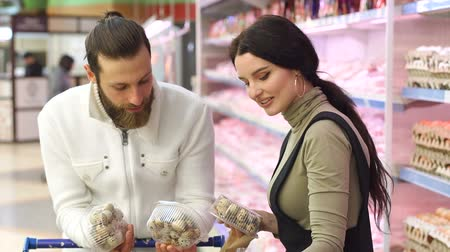 cow boy : Young happy couple choose quail eggs in supermarket. Young family buying eggs at the grocery store. Slow motion. Portrait.