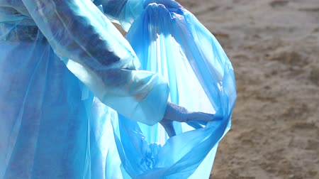 coletando : Close-up of a young woman in gloves and a special robe cleaning garbage on the beach, she holds a large blue garbage bag. Woman picking up trash and plastics cleaning the beach with a garbage bag. Stock Footage