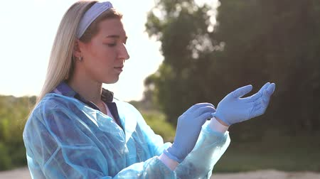 voluntary : A volunteer girl wears blue gloves before picking up trash on the beach at sunset. Volunteers help clean up garbage from parks and beaches. Slow motion. Keeping the environment clean. Stock Footage
