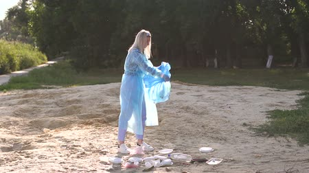 coletando : A volunteer girl in a Bathrobe and gloves collects garbage on the beach in a blue garbage bag. Environmental volunteer activist against climate change and the pollution of the oceans. Slow motion. Stock Footage