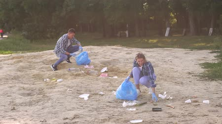 çevre kirliliği : Group of people picking up trash in the park. Volunteer community service. Group of young volunteers picking up trash on the beach. Group of young people cleaning beach area. Slow motion. Stok Video