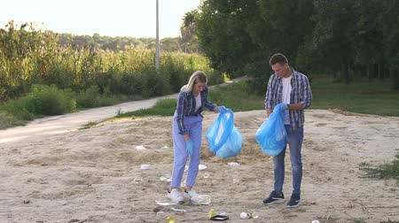 coletando : Group of young volunteers picking up trash on the beach. Woman and man wearing gloves are cleaning the beach in the Park by the lake. Slow motion.