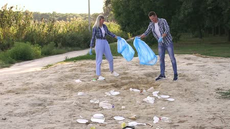 voluntário : Cheerful young people clean up garbage on the shore of a small lake in the Park at sunset. Slow motion. Group of people picking up trash in the park. Volunteer community service. Stock Footage