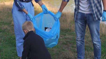 activist : A little boy in gloves helps volunteers collect plastic garbage in the Park. Parents and son volunteers collects plastic garbage on nature to save environment from pollution. Environmental damage.