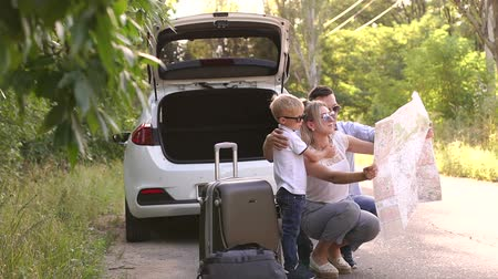 direkt : Portrait of a young family with a paper map near the car on an empty road in the woods. Father shows wife and son the travel route. Slow motion.