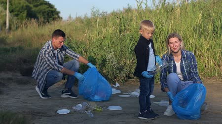 voluntário : Volunteers and children of an environmental protection group are cleaning the riverbank of garbage and trash. Mother and child help picking up trash at park. Ecology and safety for future generation.