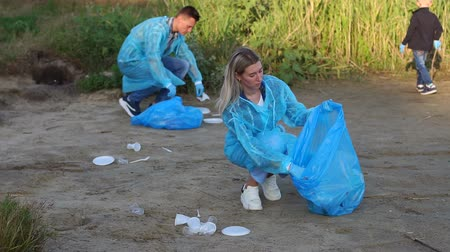 voluntário : A group of environmentalists in special clothes collect garbage on the banks of the river in a Park outside the city. Volunteers with a child help clean up plastic garbage in the Park.