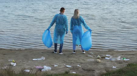 voluntário : Two volunteers in blue robes and gloves stand on the riverbank among the garbage. Irresponsible tourists throw garbage in nature. Environmental pollution. Volunteer concept. Stock Footage