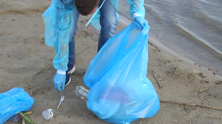 voluntário : Close-up of a male ecologist or volunteer collecting plastic garbage from a river or lake. A man volunteer in gloves helps to clean the beach of debris and waste. Stock Footage