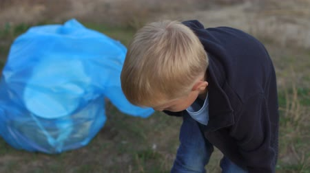 voluntário : Close-up of a small responsible boy helping to clean up the garbage in the Park near the river. Volunteers with children collect plastic garbage on the beach. Ecology and safety for future generation.