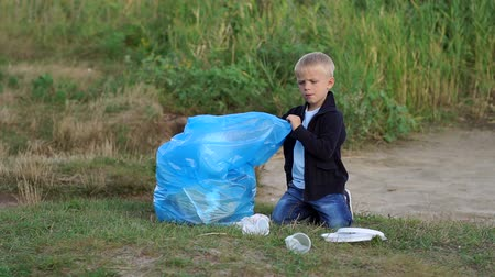 voluntário : Portrait of a cute boy who helps to collect plastic garbage in the Park on the beach near a small lake. A child volunteer cleans the Park of garbage and rubbish. Environmental protection. Stock Footage