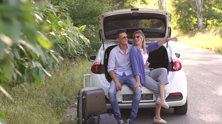 bavul : A happy couple is sitting in the trunk in a car on an empty road, a suitcase and a travel bag are standing nearby. A couple travels by car. The girl points a finger somewhere.