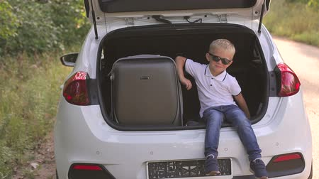 bavul : Adorable little kid boy in a sunglasses sitting in car trunk before leaving for summer vacation with his parents. Happy child with suitcases going on journey. Happy family traveling. Stok Video