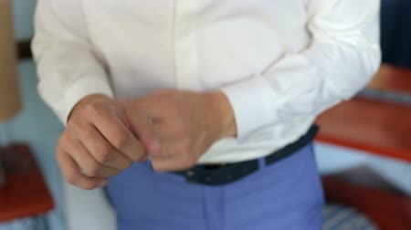 manşet : Businessman buttoning buttons on shirt sleeves, close-up. A successful man in a white shirt fastens buttons on the sleeves, close-up.