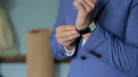 laços : Close-up of a successful man is putting on a wristwatch. Mens hand with a watch, watch on a mans hand, putting the clock on the hand.