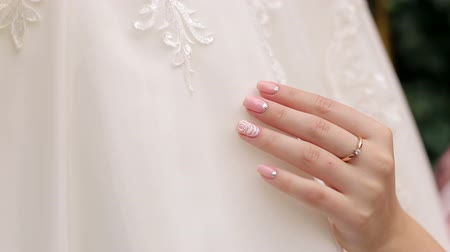sentiment : Bride holding and admiring her beautiful wedding dress in front of the window. Close-up of hand with delicate manicure. Wedding morning. Gorgeous bride is getting ready for wedding.