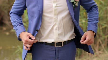 manşet : A man buttoning his jacket in the Park in summer, close-up. Successful young man puts on a suit jacket.