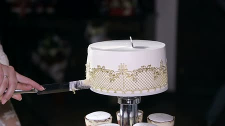 elegant dessert : Couple hands cutting wedding cake. The newlyweds cut a beautiful white wedding cake. Close-up.