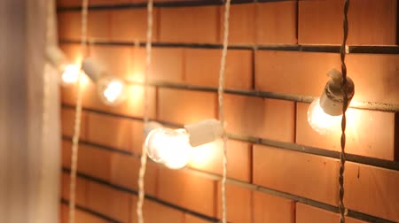hanglamp : Brick wall with a garland of light bulbs. Lights Decorations for Celebratory design. Light bulbs near the brick wall. Incandescent bulbs on brick wall background in loft style.