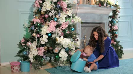 ártatlan : Portrait of happy mother and adorable baby celebrate Christmas. New Years holidays. Toddler with mom in the festively decorated room with Christmas tree and decorations. Mother playing with baby boy.