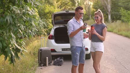 tea bag : A young couple in love drinking tea or coffee from a thermo cups standing near the car on the side of the road in the woods on an empty road. In the background, a car with an open trunk and a suitcase