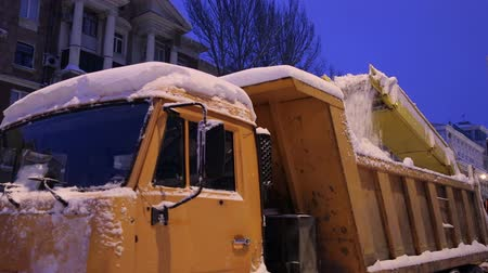 муниципальный : Close-up process of working snow plow. Snow plow loads snow into the truck body. City workers clearing snow from the roads after heavy winter snowfalls. Стоковые видеозаписи
