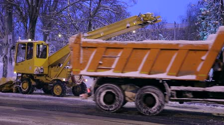 snow plow : Tractor cleaning the road from the snow. Excavator cleans the streets of large amounts of snow in city. Removing snow with plow, at night. Close-up. Stock Footage