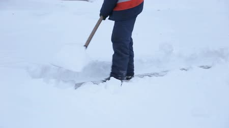 kehren : Workers sweep snow from road in winter, Cleaning road from snow storm. Roads and sidewalks covered with snow. Worker shovel clears snow.