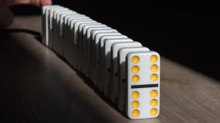 dobbelstenen : A men pushes a Domino and starts a chain reaction on the floor in a patch of sunlight. Sun ray. Close-up. Slow motion. Dominoes. Chain reaction. The Domino Principle. Board game. Falling dominoes. Stockvideo