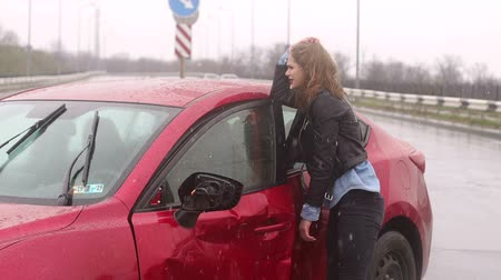 prawo jazdy : The wounded girl stands near the broken car in the rain, she is wounded and holds her head. A frightened girl is in shock after a severe accident on the road outside the city. Slow motion. Wideo