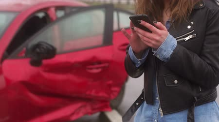 karetka : Close-up of a girl in a car accident holding a phone and asking for help. The girl is standing with a phone on the background of a broken car on road in the rain, her hands were frozen from the cold.